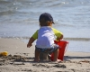 child on the beach building a sand castle